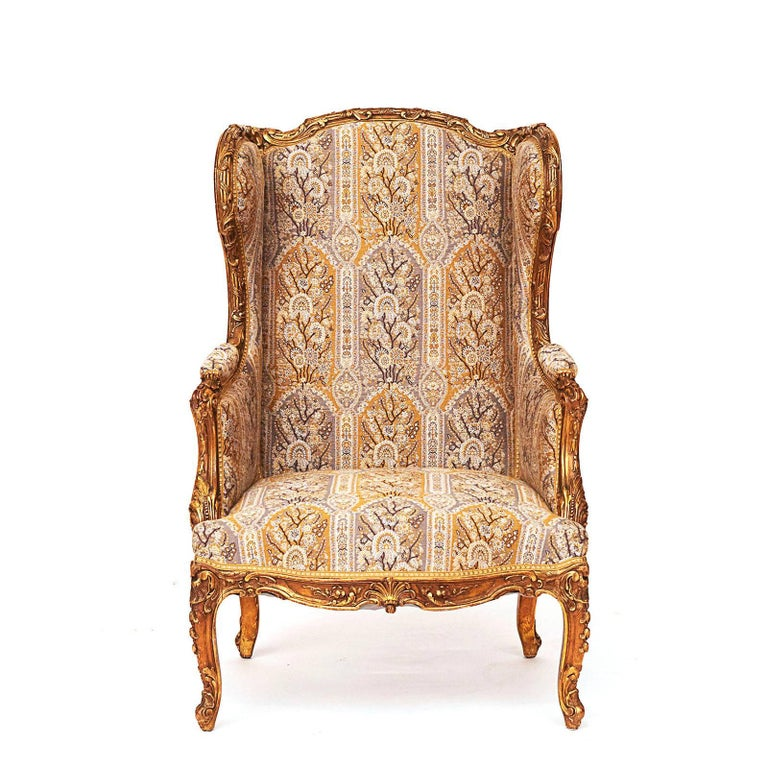 A French Napoleon III carved and giltwood wing chair, circa 1870s, with an arched carved top, curved wigs raised on scrolled supports, carved and curved frieze raised on cabriole legs. Good patina on gilded surface. New upholstery by G.P & J Baker.