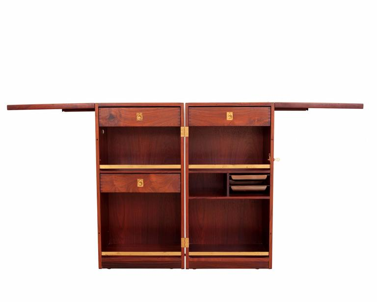Rosewood bar on wheels with drawers with brass fittings and unfolding table tops with black formica. 
