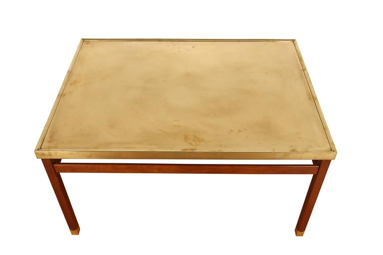 Unique rectangular coffee table. Brass top with moulded edges rests upon square Cuban mahogany legs including brass shoes with wavy lines. Legs connected by decorative stretchers.  Manufactured by master cabinetmaker Jacob Kjær. Date of