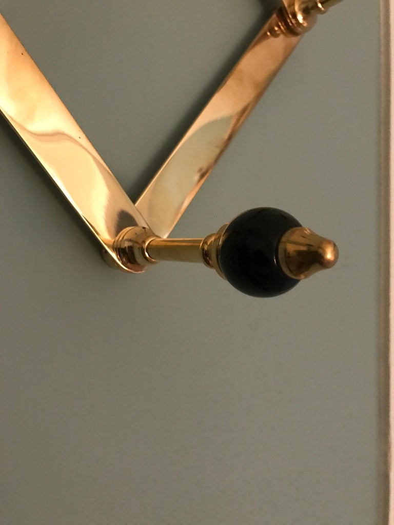 Elegant coat hanger in polished brass and black lacquered wooden knobs. Designed by Luigi Caccia Dominioni in the 1960s for Azucena.