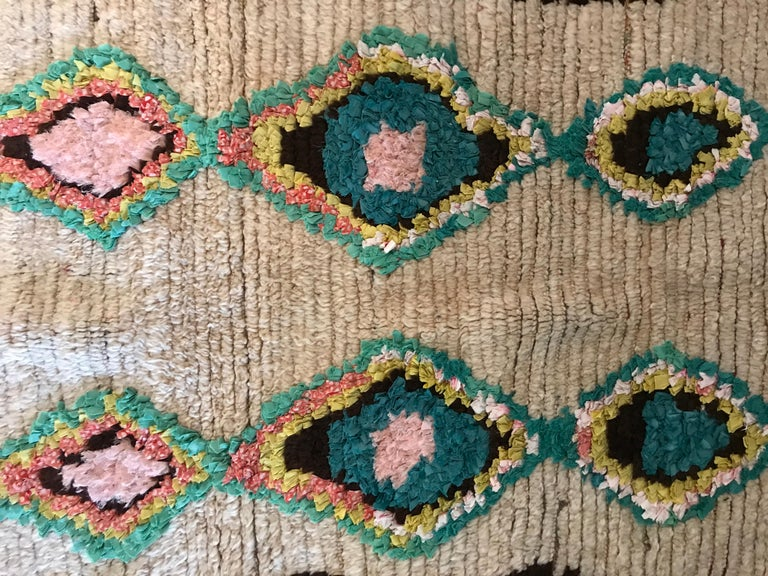 Beautiful vintage Ourika rug with brown stripes in each side and a white middle piece with a diamond shape pattern in adorable pastel colors.