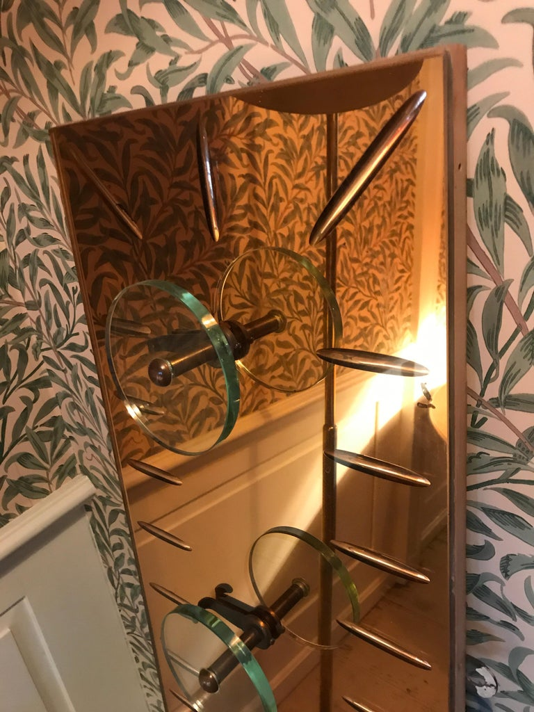 Beautiful coat hanger with four circular glass pegs and brass hooks. Rose tinted mirrored glass.