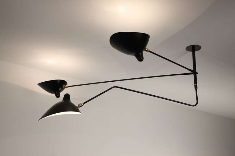 Licensed edition from Serge Mouille's original design. Pre-curser of the ceiling three arms, the ceiling two fixed arms with one curved and rotating arms has seen a great regain of interest.