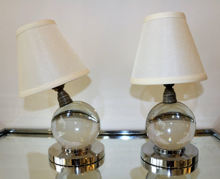 This pair of table lamps by Jacques Adnet & Baccarat is an icon of the modernist Art Deco style. Each lamp is made of a solid globe of glass simply lying on a chromium plated metal base. It can be put in any position. The shades are new. Wired for