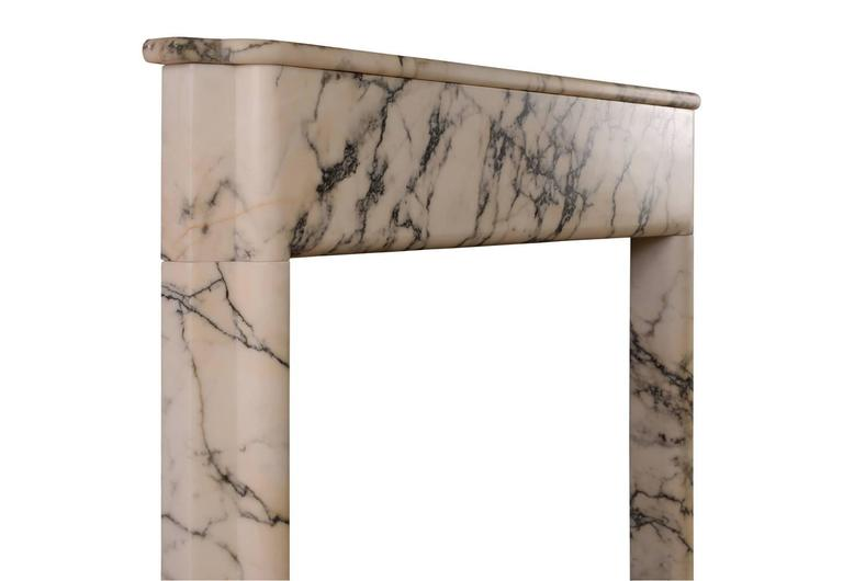 A rarely found English, early 20th century Art Deco fireplace in Italian Pavonazzo marble. The moulded jambs surmounted by plain frieze and shaped shelf above.  Shelf width - 1359 mm  53 ½ in. Overall height - 1311 mm  51 ⅝ in. Opening height -
