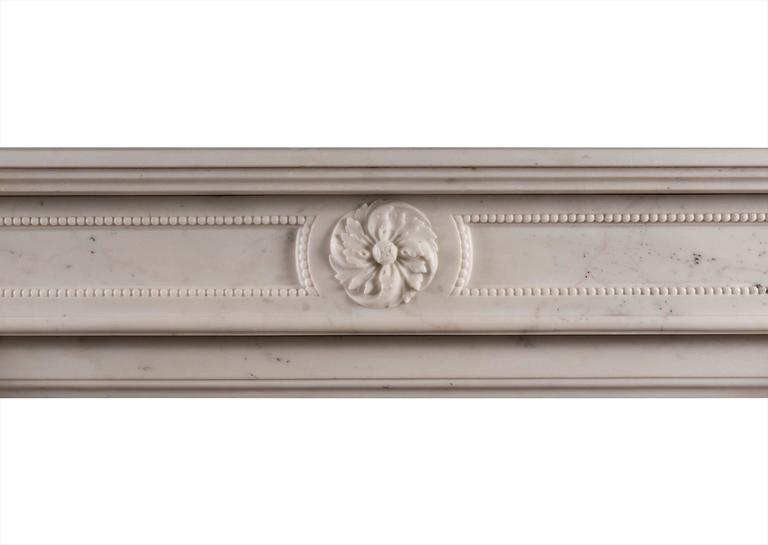 An elegant Statuary white marble fireplace in the Louis XVI style. The shaped jambs with carved rope moulding t0 centre, surmounted by carved swirling paterae to end blocks. The panelled frieze with matching patera and fine beading. Moulded shelf,