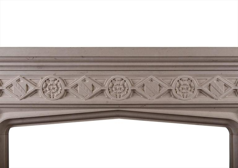 A carved limestone fireplace in the English Gothic style. The diamond shaped frieze with shields and Tudor roses with moulded jambs. Moulded shelf above. A copy of an earlier piece.  Measures: Shelf width 1572 mm 61 in Overall height 1334 mm 52 ½