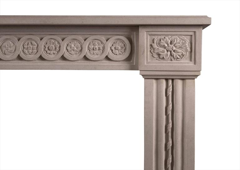 A well-proportioned French Louis XVI style fireplace carved in Portland stone. The carved frieze of guilloche and paterae, shaped jambs of reeded form with carved rope moulding, surmounted by oval pateras. A copy of an 18th century original.  Shelf