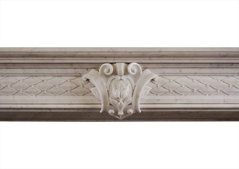A 19th century white marble fireplace. The jambs and frieze with carved leafwork and berries throughout and carved cartouche to centre. Moulded shelf above.  Measurements: Shelf width - 1735 mm / 68 1/4 in. Overall height - 1195 mm / 47 in. Opening