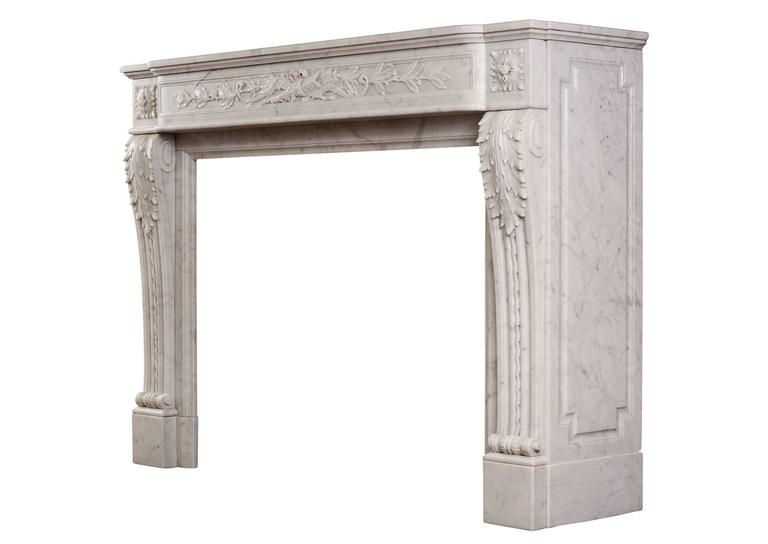 A mid-19th century French Louis XVI style Carrara marble fireplace, with panelled frieze delicately carved with quiver, arrow and foliage. The shaped jambs with acanthus leaves, rope moulding and square paterae above. Moulded