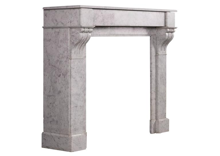 A petite French, Louis Philippe Carrara marble fireplace. The jambs with scrolled brackets to top, surmounted by plain frieze and moulded shelf. Early/mid-19th century. Well suited for a bedroom or smaller study.  Measures: Shelf width 1111 mm 43