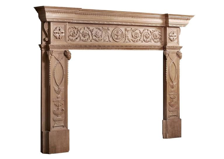 An imposing period English Regency pine fireplace. The finely carved jambs featuring urns and swags surmounted by carved rams heads, the end blockings with carved round paterae, the frieze with delicately carved floral scrolls and winged