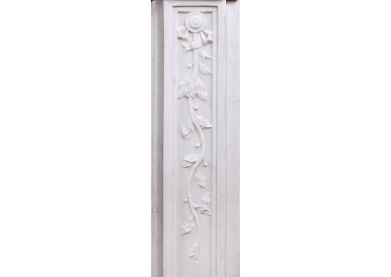 An elegant late 18th century period Louis XVI Statuary marble fireplace. The panelled frieze and jambs with trailing vine leaves, the frieze with centre motif of scrolls and leaves, and the jambs with tied ribbons to top.  Measures: Shelf width