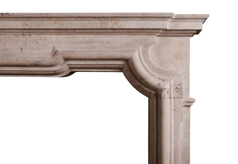 A good quality Italian fireplace in the Baroque manner in white travertine stone. The shaped frieze with heavy moulding and breakfront shelf above. A substantial piece. Modern. N.B. May be subject to an extended lead time, please enquire for more