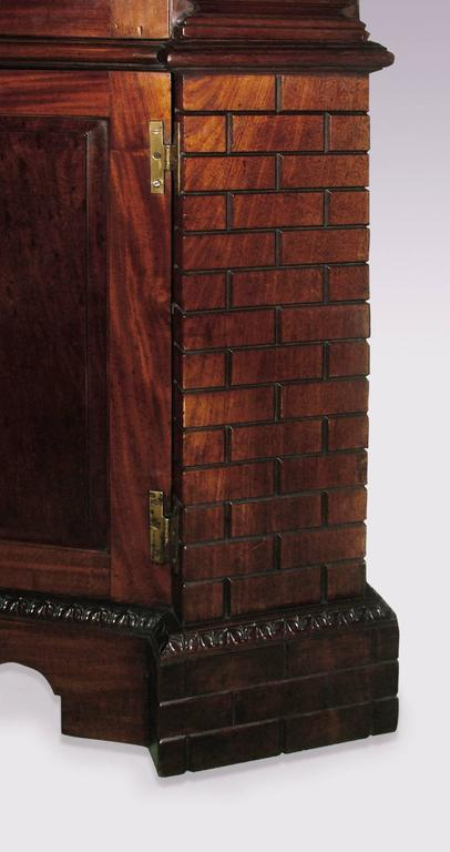 """An important mid-18th century mahogany corner cupboard having dentil moulded cornice above fielded plum-pudding mahogany panels, flanked by fluted columns to upper section and unusual """"rusticated"""" canted corners to the lower section, raised on"""
