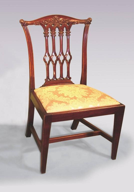 A set of eight 19th century Chippendale style mahogany dining chairs having moulded, floral carved backs with pierced, Gothic, fleur-de-lys carved splats above drop in seats.