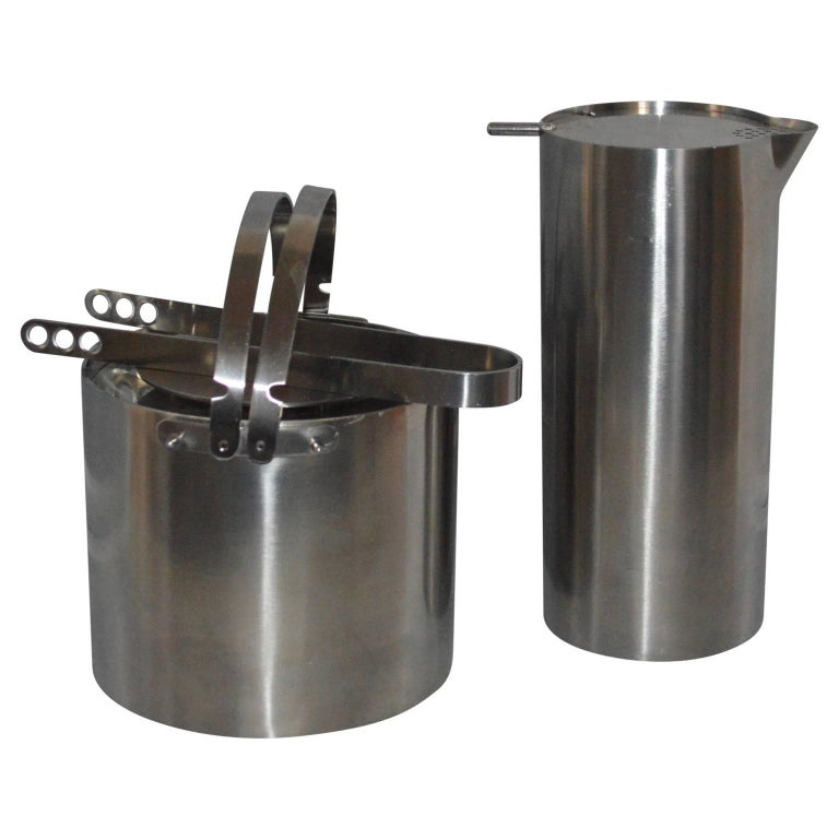 Arne Jacobsen for Stelton Pitcher, ice bucket and tongs. The ice bucket, tongs and pitcher are in stainless steel and marked Stelton, Denmark. The ice bucket has double handles and lid, tongs fit inside the interior of the bucket. This set is in