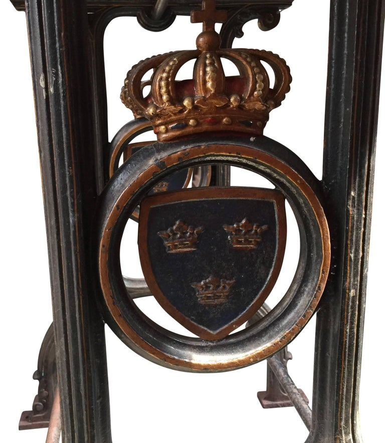 Charming iron cast table, with a crowned emblem with three royal Swedish crowns on blue background on each side.