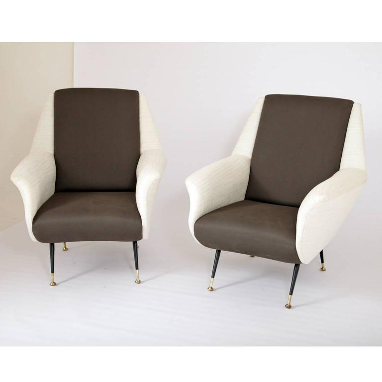 Pair of Italian lounge chairs on thin iron feet. Backrest and seat are dark grey, the sides are white.