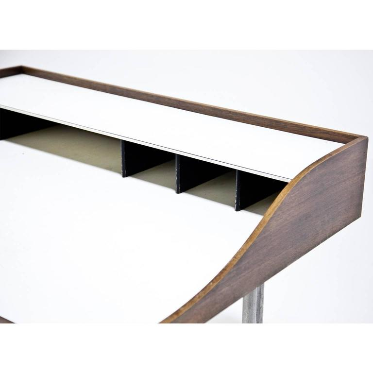 The famous 'Swag-Leg' desk by George Nelson, designed in 1954 for Hermann Miller. The iconic legs are metal, the dividers are in a dark brown color. Both drawers have the plastic inlays. The table shows wear consistent with age and use. The table is