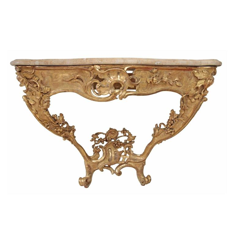 Exceptional Rococo console table with rosé-colored marble top. The asymmetrical giltwood base is decorated with rocaille, fruit and leaves decor.