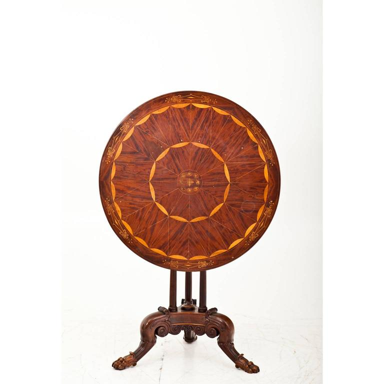 Very beautiful side table on a carved trefoil stand with paw feet. The foldable round tabletop shows a beautiful inlay work out of maple.