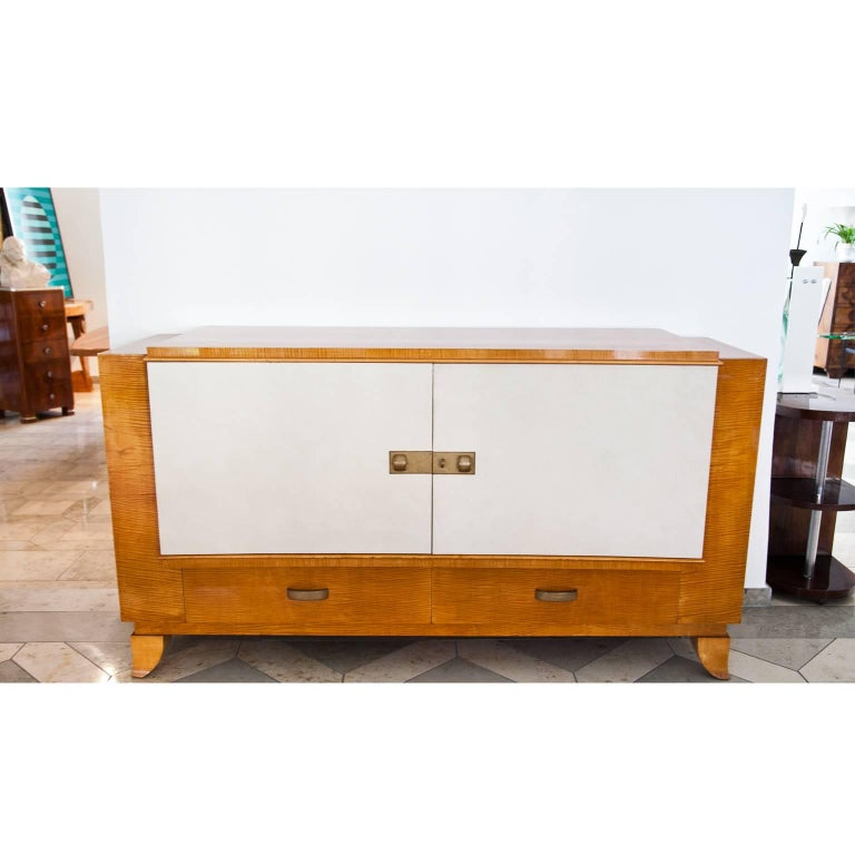 Art Deco sideboard on curved feet with two drawers and a middle compartment with two doors. These are covered in a light colored faux leather.
