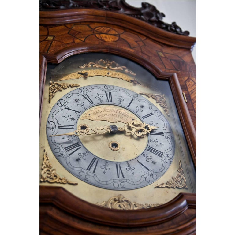 Grandfather clock with carved top and decorated with inlaywork. The clockface with Roman numerals reads Non Repet Repeto Taceo Audio and Baumgartinger Mergentheim.