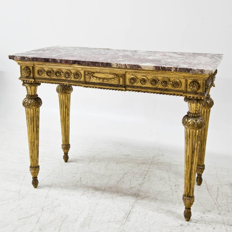 Gilt Louis Seize console table on fluted legs, the front rail is decorated with interlaced ornaments, flowers, festoons and beads. The red and white marble top completes this beautiful piece of furniture, it was added later in the 19th century.
