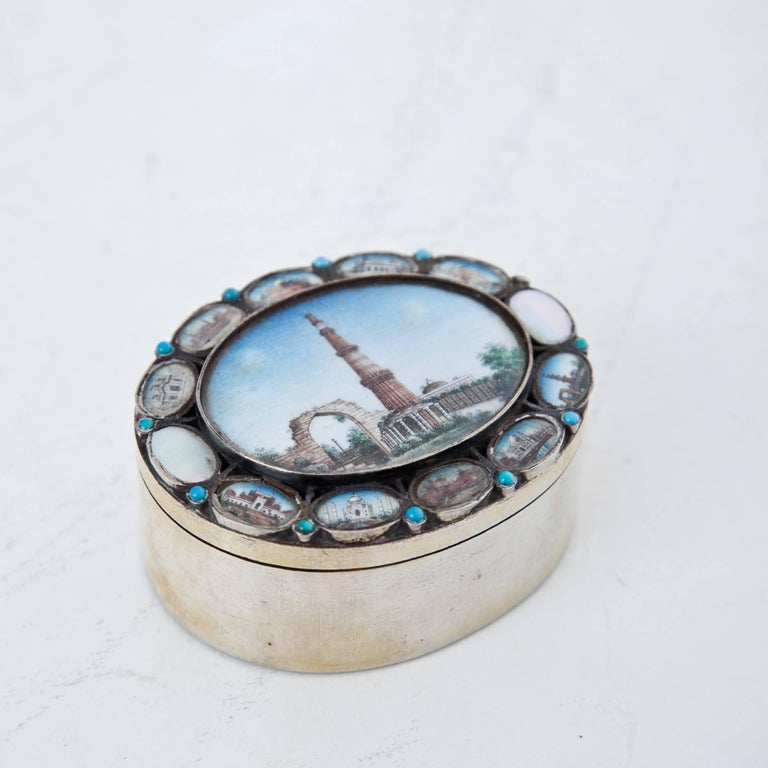 Oval silver box with miniature depictions of important monuments of India. In the center is a large depiction of Qutb Minar, the famous watchtower of Delhi. In the smaller medallions, one can find among others a depiction of the Taj Mahal.