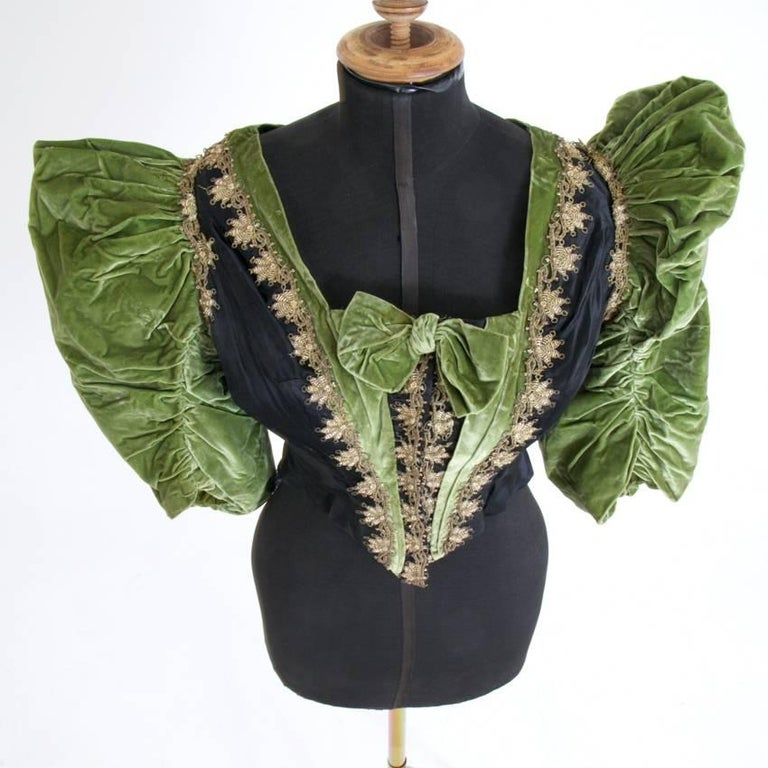 Black silk Bodice with puffed sleeves out of green suede in a very well preserved condition. The bodice is decorated with floral details out of gold thread and tiny pearls. A label written in black ink dates the bodice to 1888, worn by Mrs.