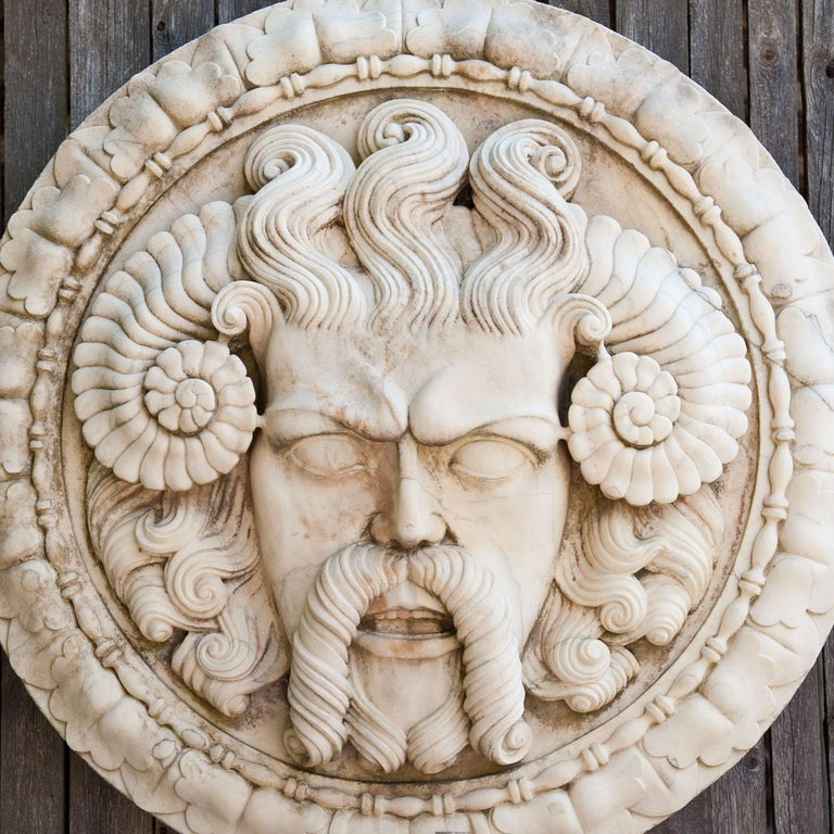 Large round marble wall relief with a leaf decorated boarder and a very expressive male mascaron with ram's horns and a curly beard and hair.