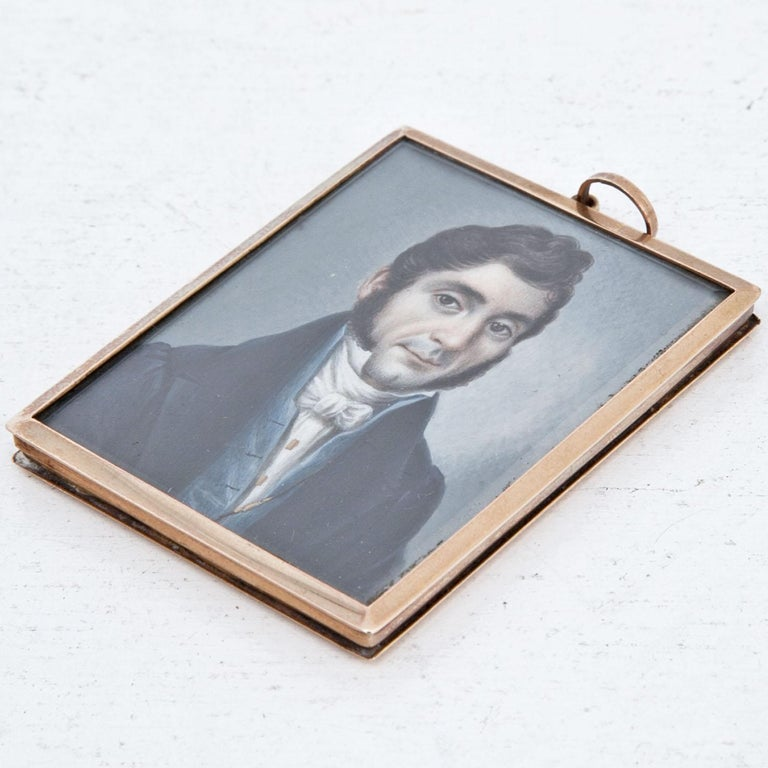 Rectangular miniature painting of a gentleman in Biedermeier clothes, with brown curly hair in front of a grey background. Brass frame.