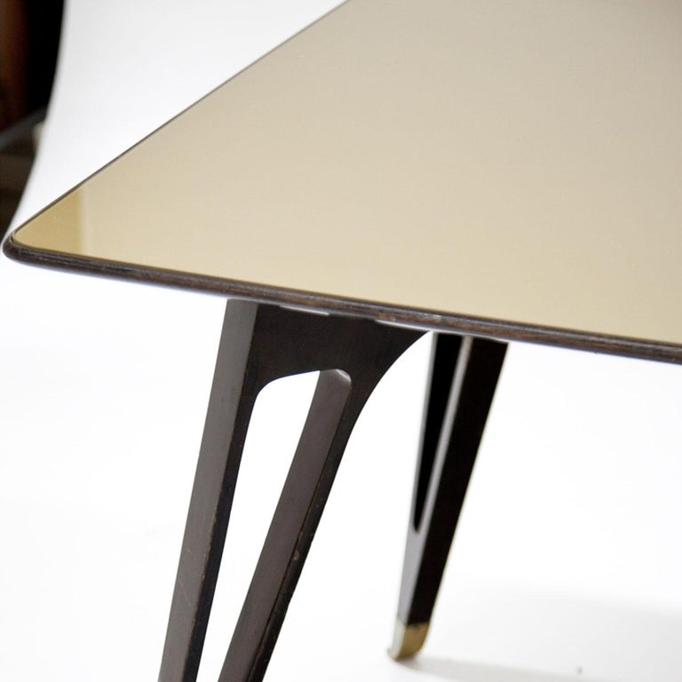 Large dining table on four legs, each with brass caps and wedge-shaped cutouts. The tabletop is covered with a tinted glass top.