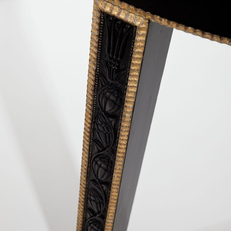 Ebonized demilune console table of the Vienna Secession, standing on three legs. The straight apron and the legs are decorated with gilt wavy profiles, the latter also with carved flowers and vines at the front. The glass top is recent.