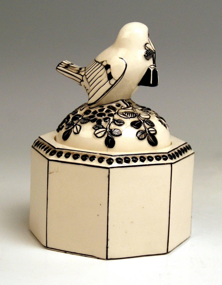 Detailed description:  Ceramics box (eight-sided), with sparrow holding a flower's twig in beak / the bird's figurine is attached to lid DESIGN: Michael Powolny, circa 1907  cream white and black shaded  The domed lid of box is abundantly