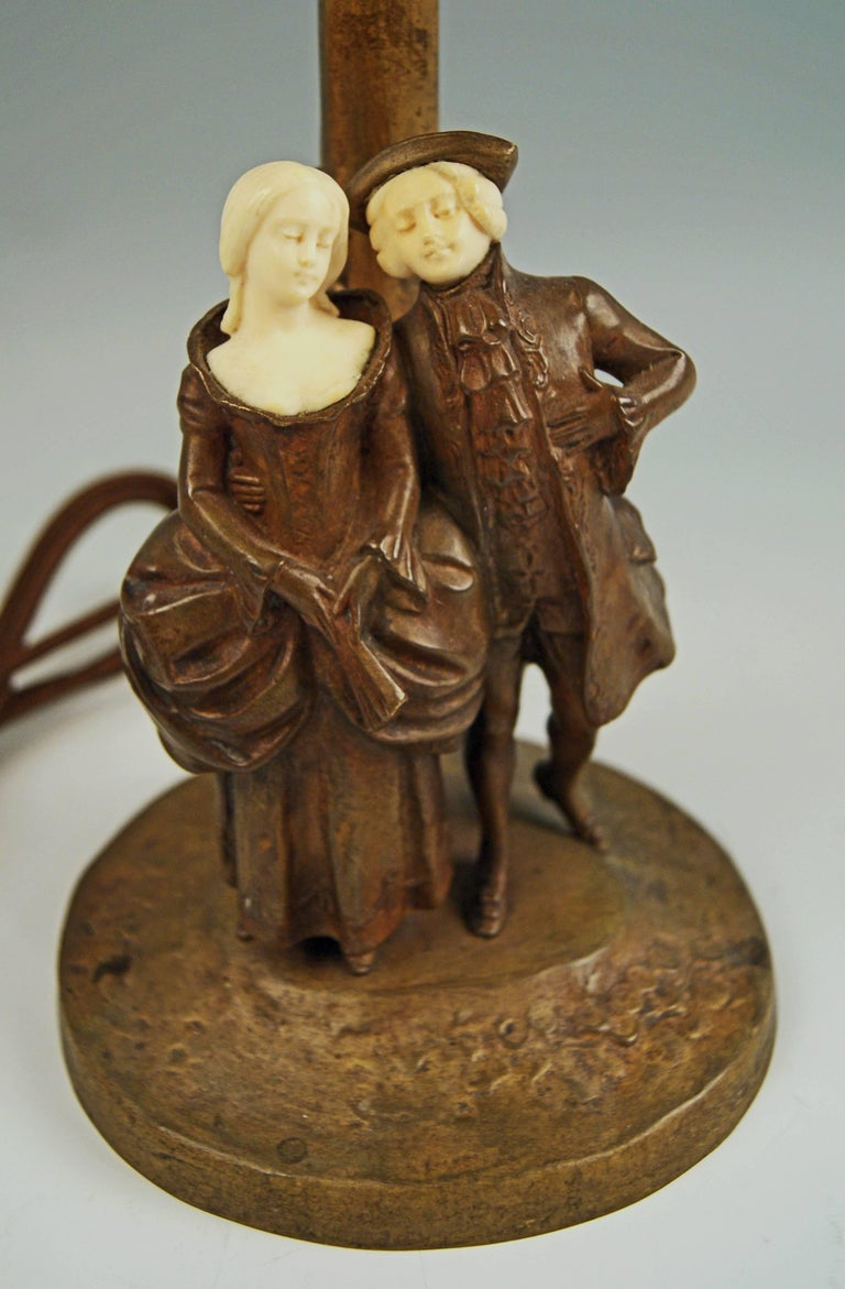 Gorgeous Vienna bronze table lamp created by famous bronze sculptor Peter Tereszczuk (1875 - 1963) made circa 1910-1915.   There are two sculptured figurines visible: both are walking whereas the man embraces woman's hip. The couple is dressed