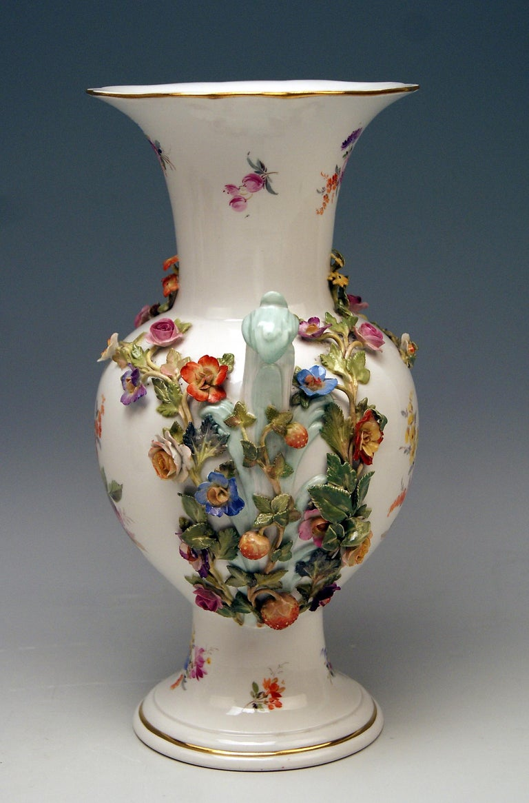 Meissen nicest vase with handles, decorated with sculptured flowers and fruits.  Manufactory: Meissen  Dating: made circa 1870 Hallmarked: Meissen Mark with Pommels on Hilts (third quarter of 19th century) First Quality model number visible,