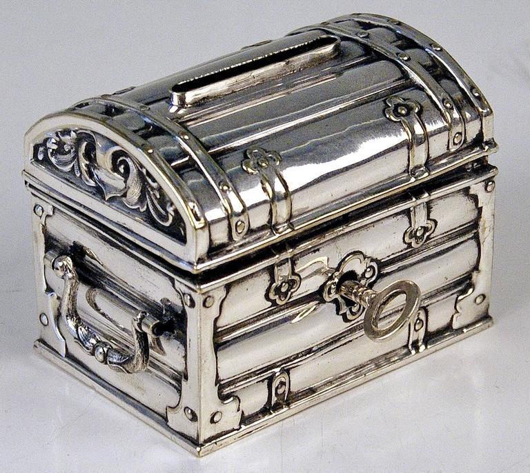 Austrian silver money box or piggy bank manufactured during later 19th century period made circa 1880-1885.  Excellently made lidded money box (piggy bank) shaped as treasure chest having movable handles at lateral sides. Original key existing /