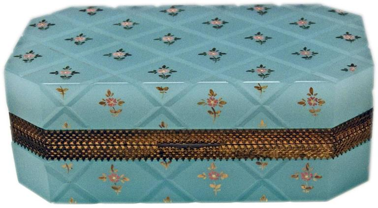 Specifications: Opaline bright blue box with hinged lid having gilt bronze mountings of very elegant appearance / the lid closes properly. The casket's surface with splayed edges has an overall crosshatched pattern with small flower's blossoms