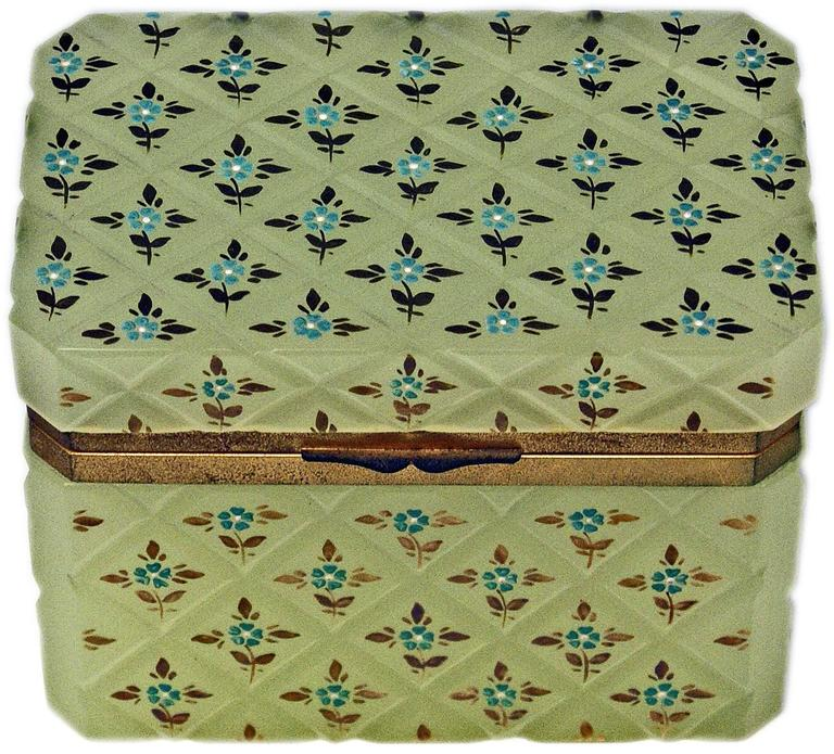 Specifications: Opaline pastel green box with hinged lid having gilt bronze mountings or the lid closes properly. The casket's surface with splayed edges has an overall crosshatched pattern with small flower's blossoms surrounded by golden leaves