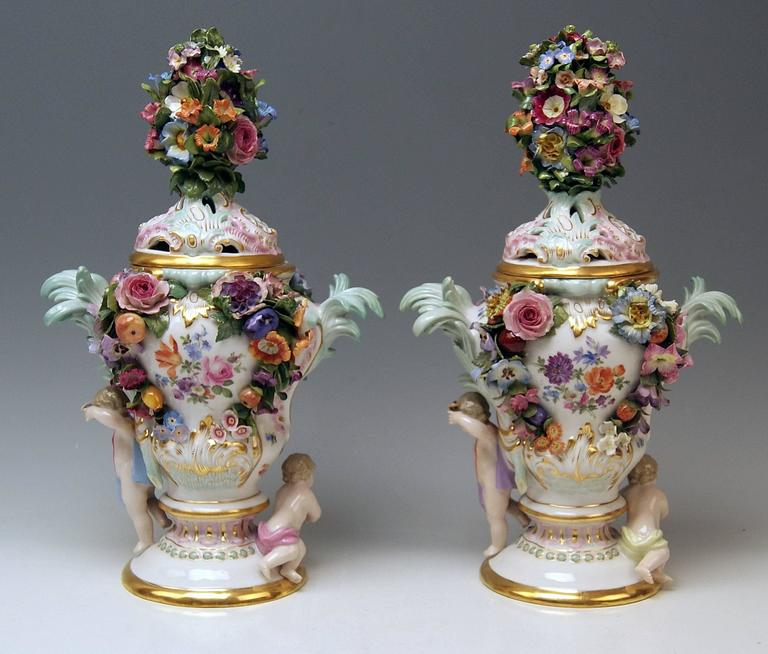 Meissen gorgeous quite rare items: a pair of potpourri lidded vases with abundant sculptured decorations as well as with nicest Watteau paintings.  Measures: Total height: 35.0 cm (13.77 inches) lid included. Total width: 22.0 cm ( 8.66