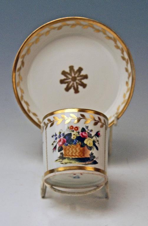 Cylindric cup with angular handle and saucer, both decorated with golden ornaments.