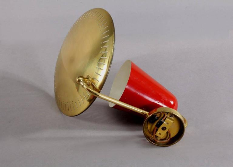 Wall lamp, attributed Arredoluce. Italy, 1950. Brass base, red laquered cone, movable reflector in brass.