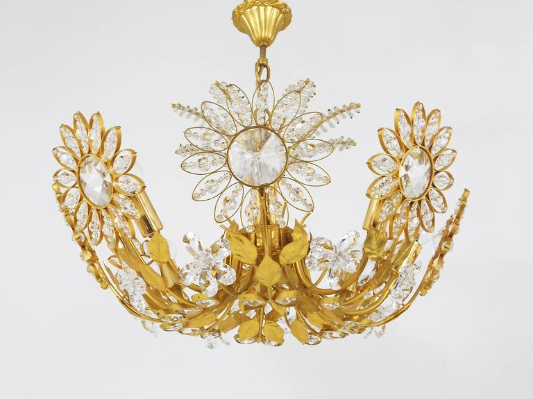A beautiful hand-crafted floral chandelier with a decorative palm tree top, manufactured in the 1970s by Palwa Germany. Made of gold-plated brass with big faceted crystal glass petals. Has eight-light-sources. In excellent condition.   Diameter