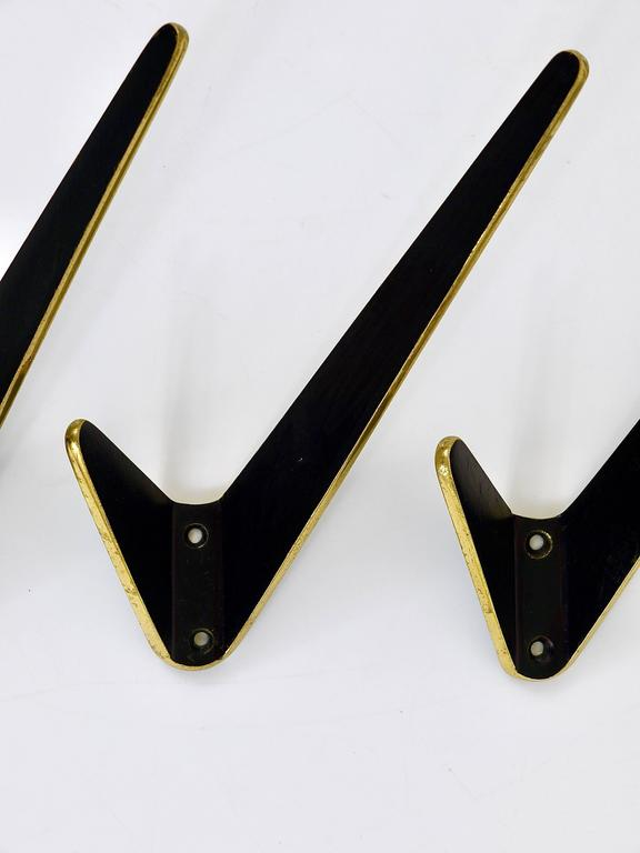 Up to five beautiful asymmetric Austrian modernist brass wall coat hooks, executed in the 1950s. Made of black finished and partly polished brass. Good condition, nice patina. Sold per piece.