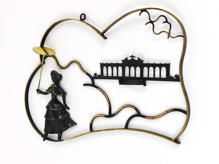 A lovely midcentury mural, displaying a woman in a Biedermeier dress with umbrella in front of the Gloriette in Vienna, all made of brass. A beautiful design by Walter Bosse, manufactured in the 1950s by Hertha Baller, Austria. In excellent