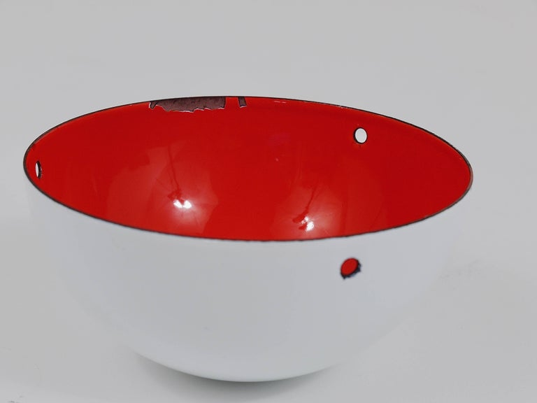 An iconic white flowerpot pendant light, designed in 1969 by Verner Panton for Louis Pulsen, Denmark. A simple but beautiful ceiling light, consisting of two enameled hemispherical lampshades facing each other. The lower lampshade has a red