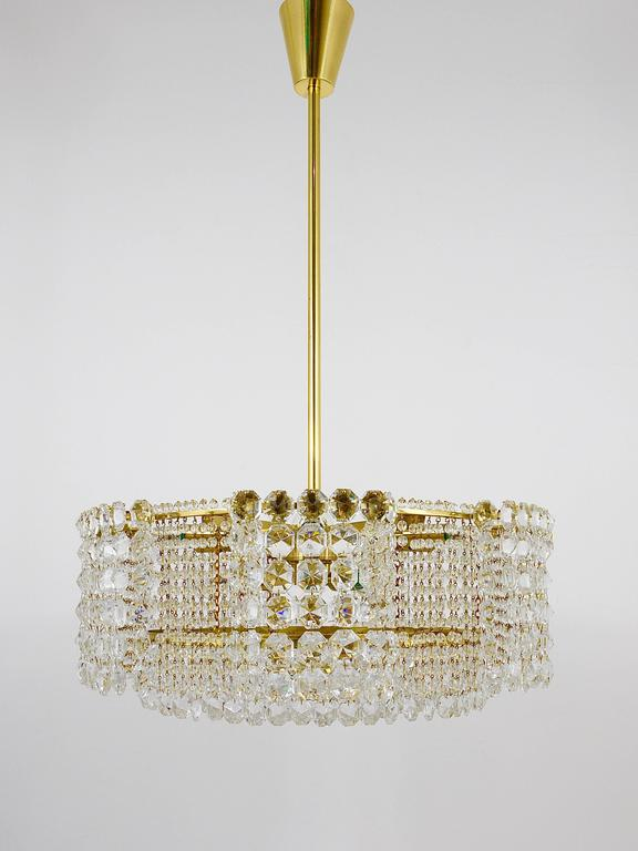 A beautiful and big multi-tiered brass and crystal chandelier by Lobmeyr Vienna from the 1950s. Fully covered by dazzling faceted crystals. This chandelier has nine light sources and has been carefully restored and rewired. In excellent condition.