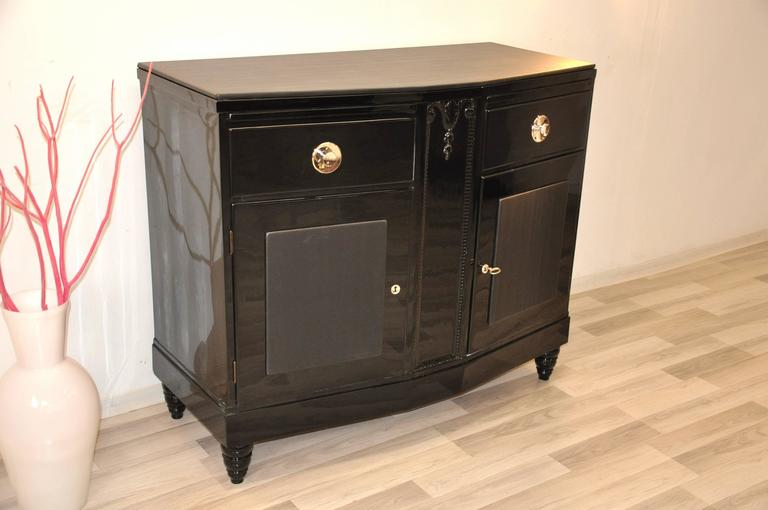 Petite Art Deco commode with wonderful ornamentation. The unique design of this masterpiece convinces with fine carved details and luxurious leather applications. The tabletop is equipped with lacquered serving extensions.  Wonderful chrome